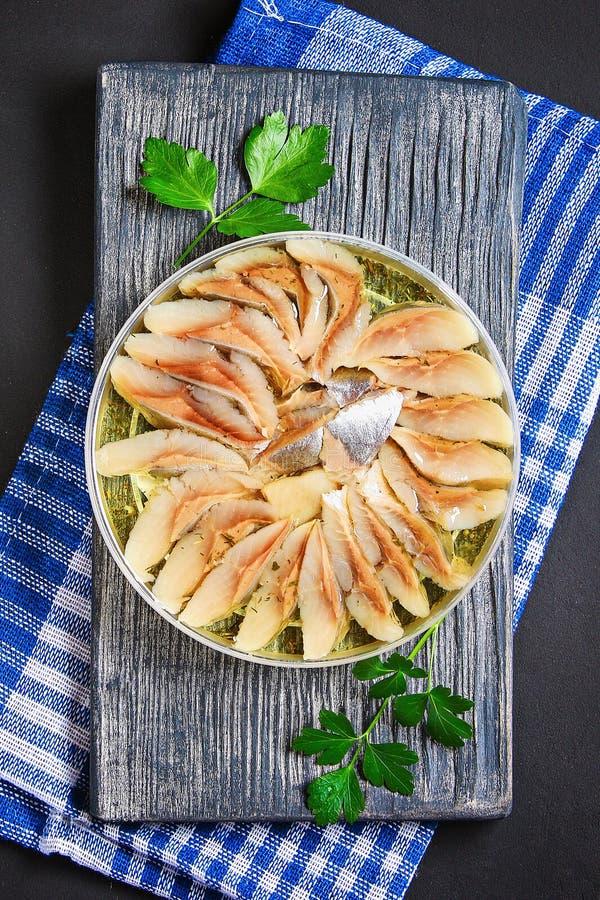 Gemarineerde haringen in olie op een houten raad op een grijze donkere lijst snack Hoogste mening De ruimte van het exemplaar stock afbeelding