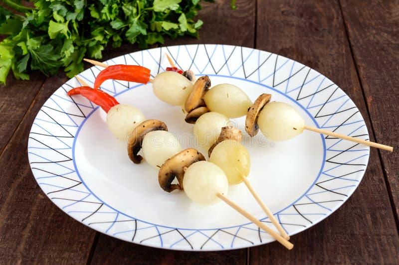 Gemarineerde kleine ui` Parel ` op bamboestokken met gebraden paddestoelen stock afbeeldingen