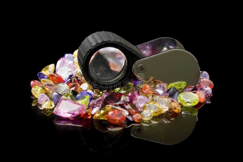 Gemas y lupa coloridas fotografía de archivo libre de regalías