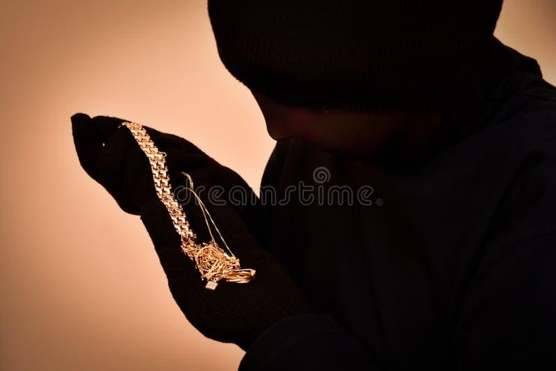 Gemaskeerde roversholding en het bekijken de gestolen juwelen stock foto