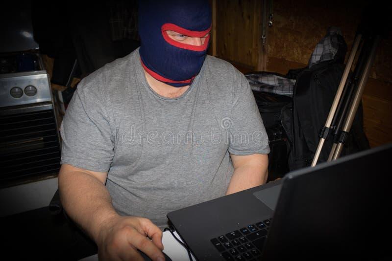 Gemaskeerde Terrorist die aan zijn computer werken Concept over internat stock fotografie