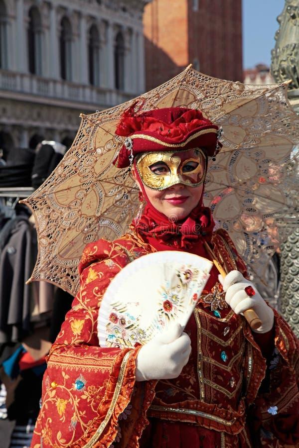 Gemaskeerde vrouw in rood kostuum met paraplu en ventilator, Venetië royalty-vrije stock fotografie