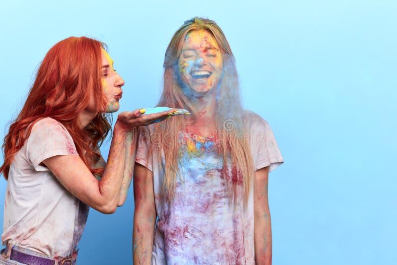 Gembermeisje die gekleurd poeder blazen aan het gezicht van haar vriend royalty-vrije stock foto