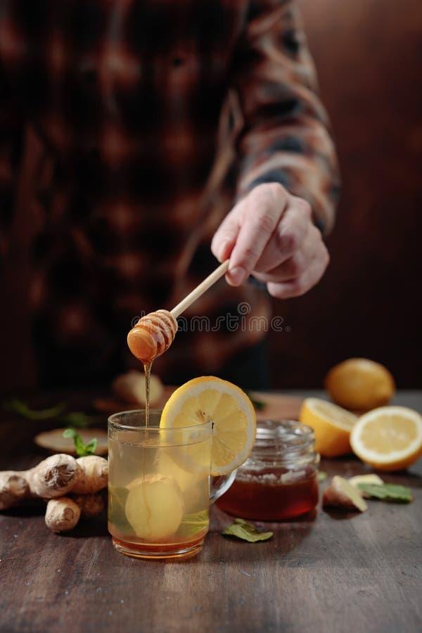 Gemberthee met honing, citroen en munt op oude houten lijst stock fotografie