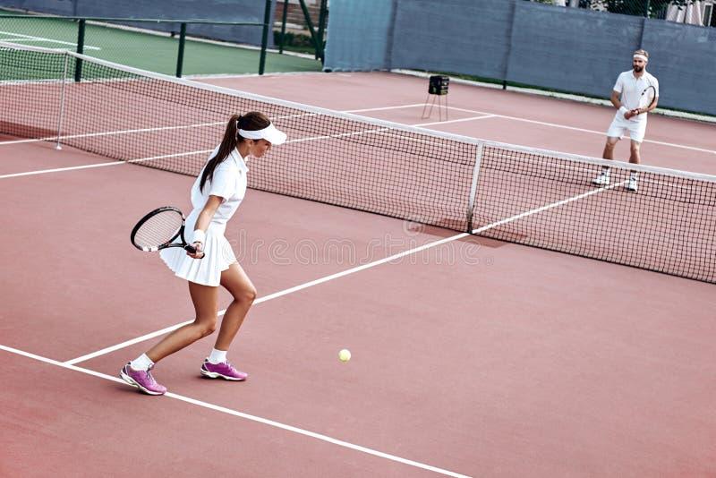 Gemeenschappelijke belangen Het jonge paar speelt tennis op het hof royalty-vrije stock fotografie