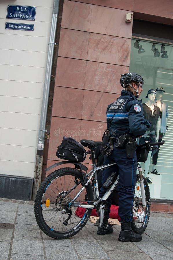 Gemeentelijke politieman die door fiets een bedelende persoon controleren royalty-vrije stock foto's