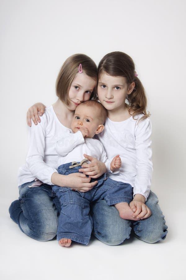 Gemella le sorelle con il fratello del neonato fotografie stock libere da diritti