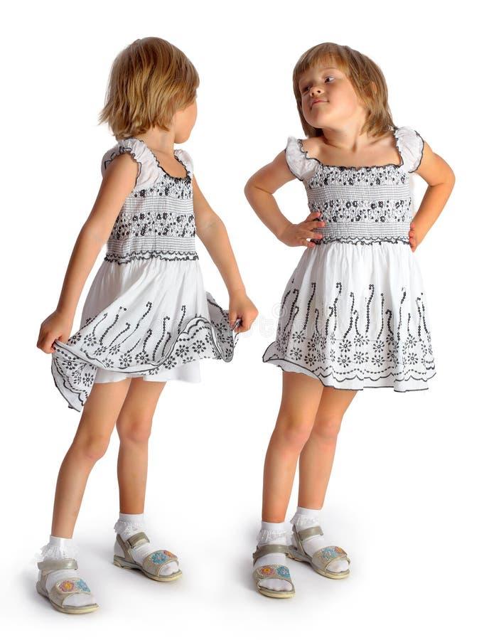 Gemelli delle sorelle nel gioco bianco dei vestiti fotografie stock libere da diritti