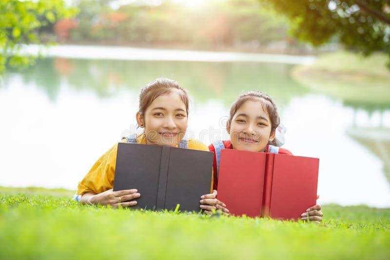 Gemelos bastante asiáticos muchacha o estudiantes que leen un libro en el público fotos de archivo libres de regalías