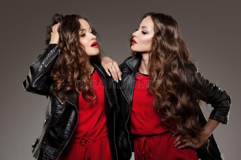 Gemelos de las hermanas en la risa del estilo del inconformista Dos modelos de manera Wom fotografía de archivo libre de regalías