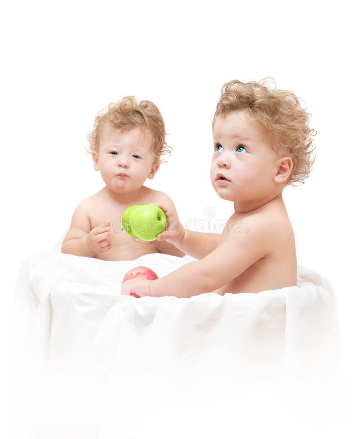 Gemelos de los niños que comen una manzana verde fotos de archivo libres de regalías