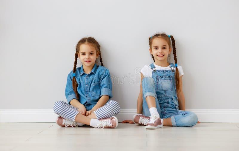 Gemelos felices de las muchachas de los ni?os de la diversi?n en la pared blanca vac?a imágenes de archivo libres de regalías