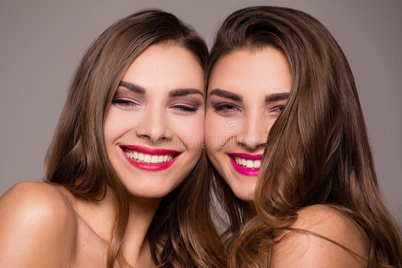 Gemelos hermosos de la hermana con sonrisa asombrosa imagen de archivo libre de regalías