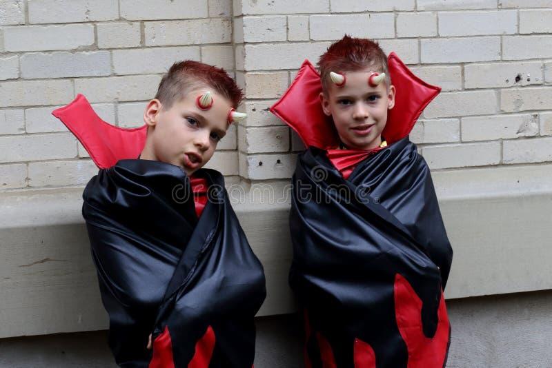 Gemelos idénticos lindos del muchacho disfrazados como diablos foto de archivo