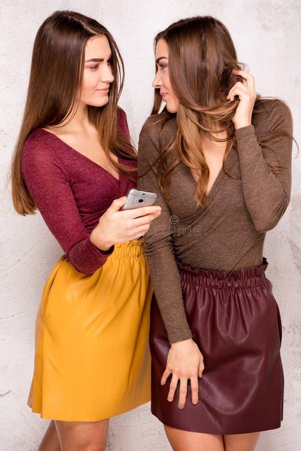 Gemelos jovenes hermosos usando el teléfono móvil fotos de archivo
