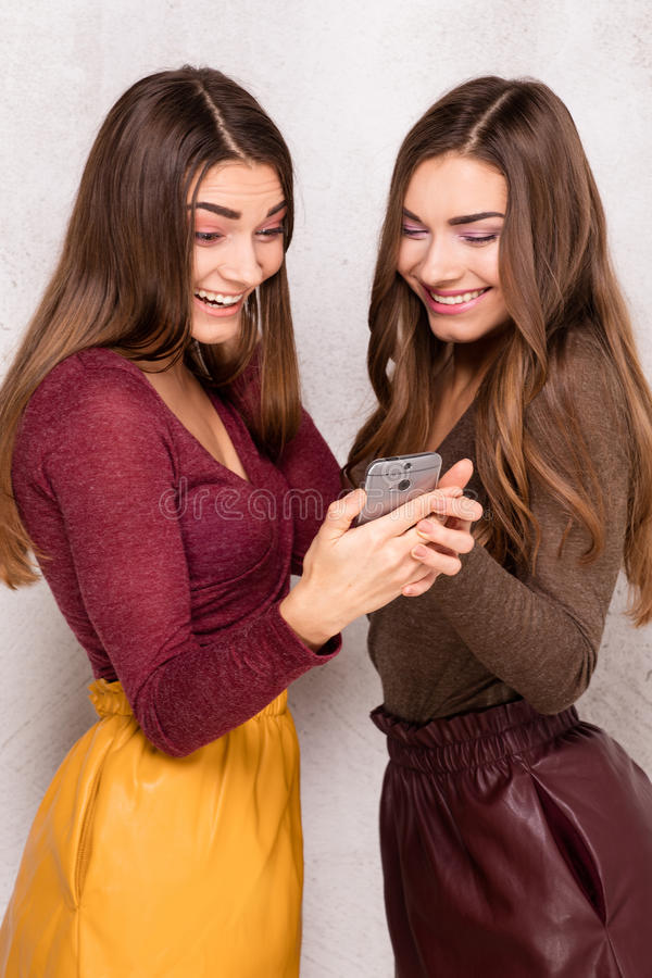 Gemelos jovenes hermosos usando el teléfono móvil imagenes de archivo
