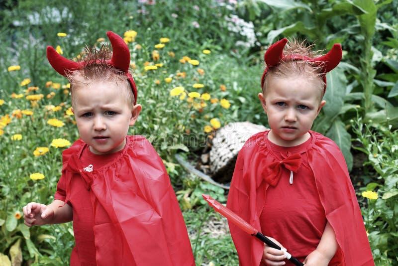 Gemelos scowling idénticos del niño disfrazados como diablos foto de archivo libre de regalías