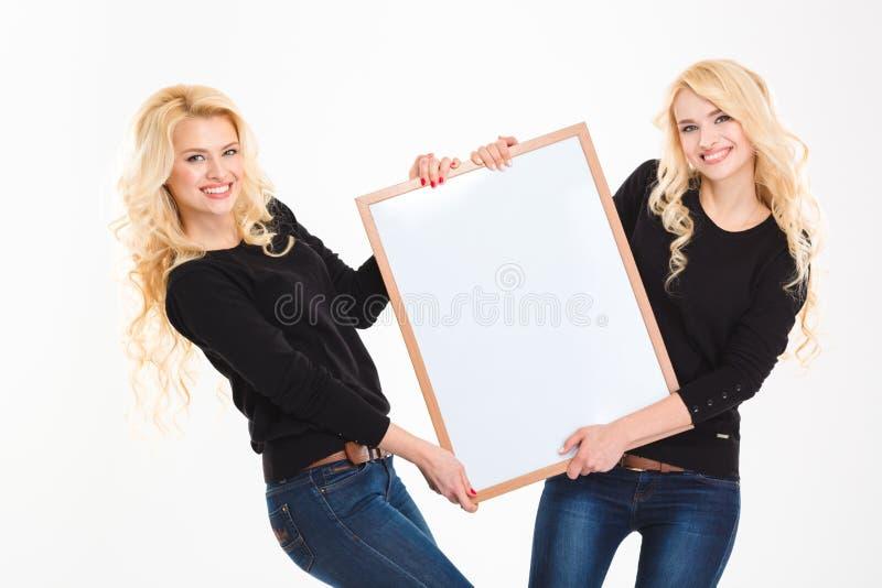 Gemelos sonrientes de las hermanas que llevan a cabo al tablero en blanco imagen de archivo