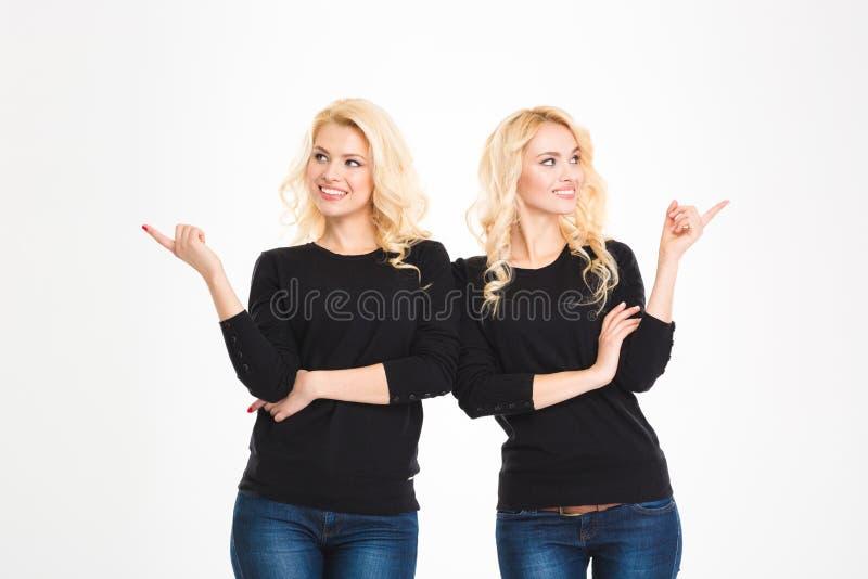 Gemelos sonrientes de las hermanas que señalan los fingeres lejos foto de archivo libre de regalías