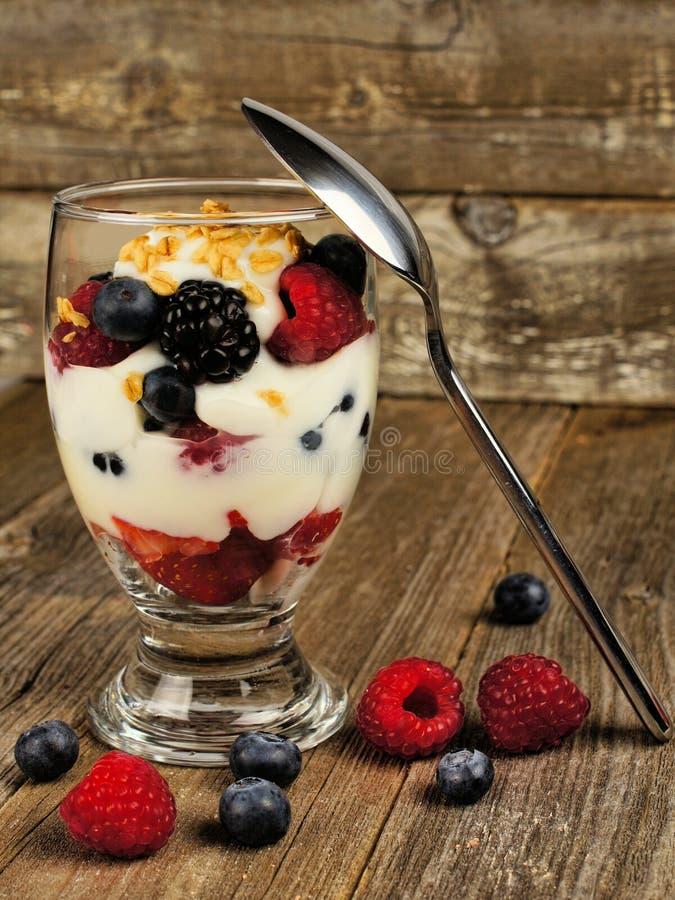Gemengd bessengranola en yoghurtparfait op hout stock fotografie