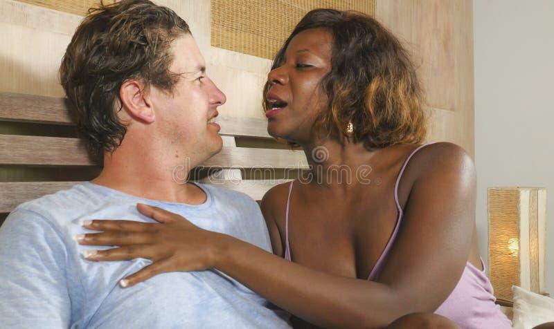 Gemengd het behoren tot een bepaald raspaar in liefde geknuffel samen thuis in bed met mooie speelse zwarte afro Amerikaanse vrou stock afbeelding