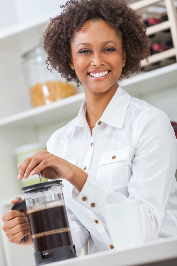 Gemengd ras Afrikaans Amerikaans meisje of jonge vrouw die met perfecte tanden in haar keuken koffie maken royalty-vrije stock foto's