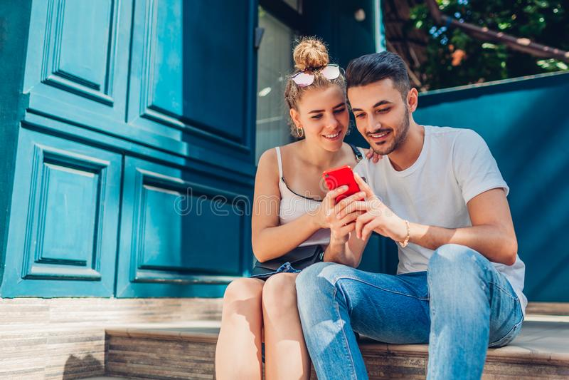 Gemengd raspaar die in liefde in stad lopen Arabische man en witte vrouw het drinken koffie en het gebruiken van smartphone royalty-vrije stock afbeelding