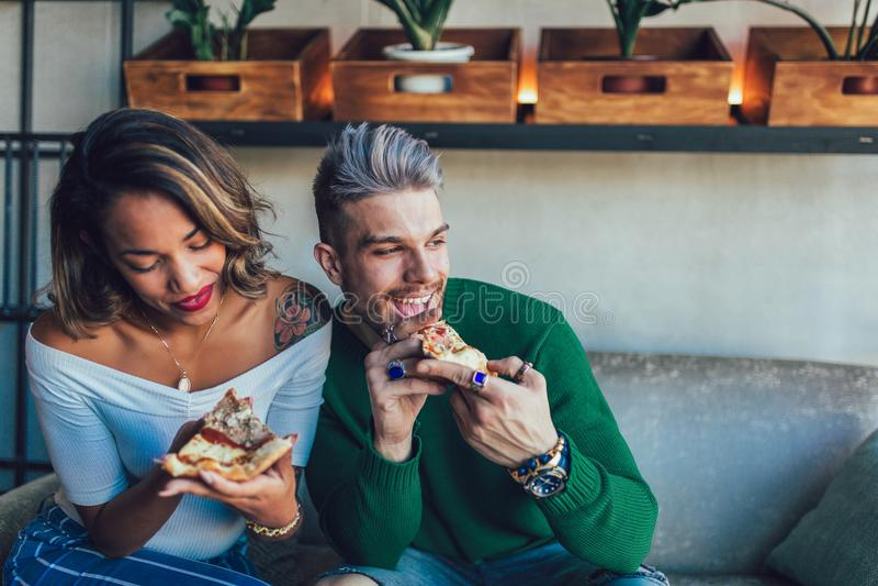 Gemengd raspaar die pizza in moderne koffie eten stock afbeelding