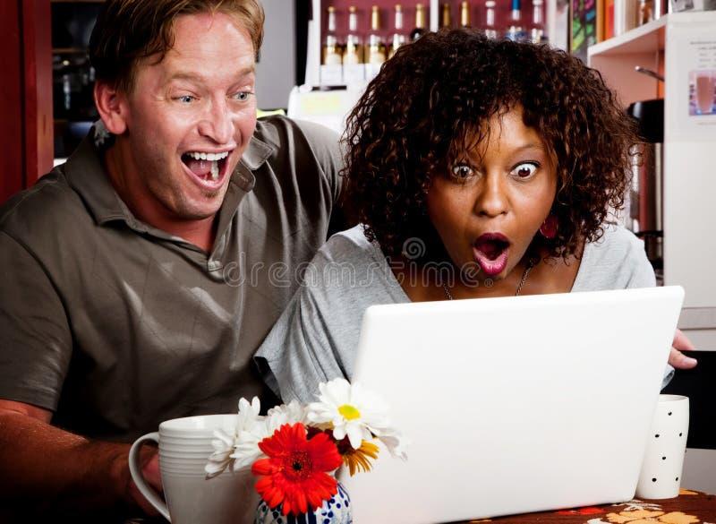 Gemengd raspaar in koffiehuis met laptop comp stock foto's