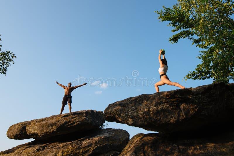 Gemengd raspaar van geschiktheidstrainers die oefeningen op de rotsachtige piek doen Sport en gezondheidszorgconcept royalty-vrije stock foto's