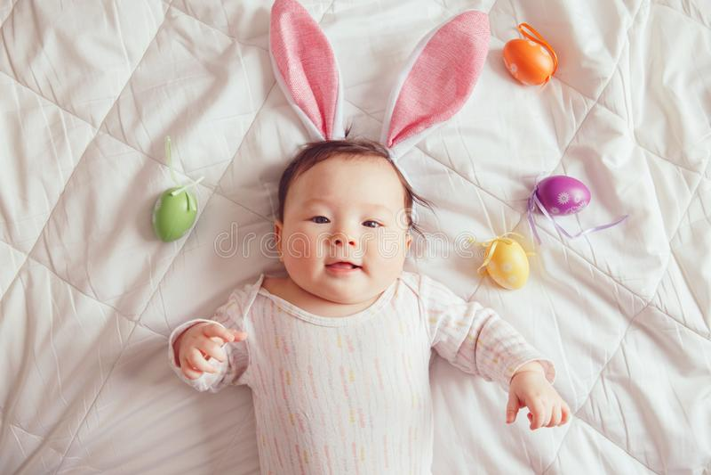 Gemengde Aziatische baby die roze Paashaasoren dragen die op bed in slaapkamer met kleurrijke eieren liggen royalty-vrije stock foto