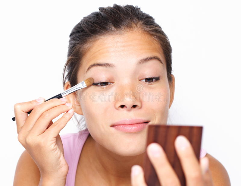 Gemengde Aziatische/Kaukasische vrouw die make-up zetten stock afbeelding