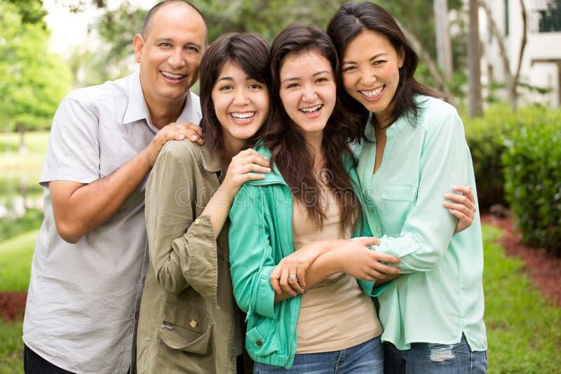Gemengde en rasfamilie die lachen huging stock fotografie
