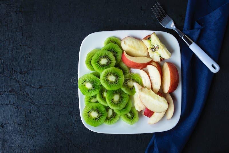Gemengde Fruit verse kiwi en appelen met druiven in een plaat op een houten lijst stock afbeelding
