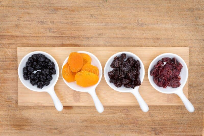 Gemengde gedroogd fruit en bessen in ceramische ramekins stock afbeeldingen
