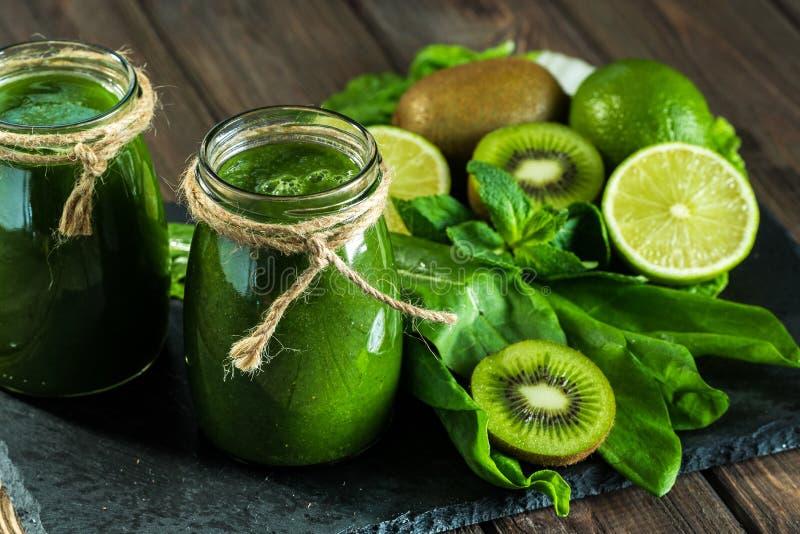 Gemengde groene smoothie met ingrediënten op de steenraad, hout stock foto