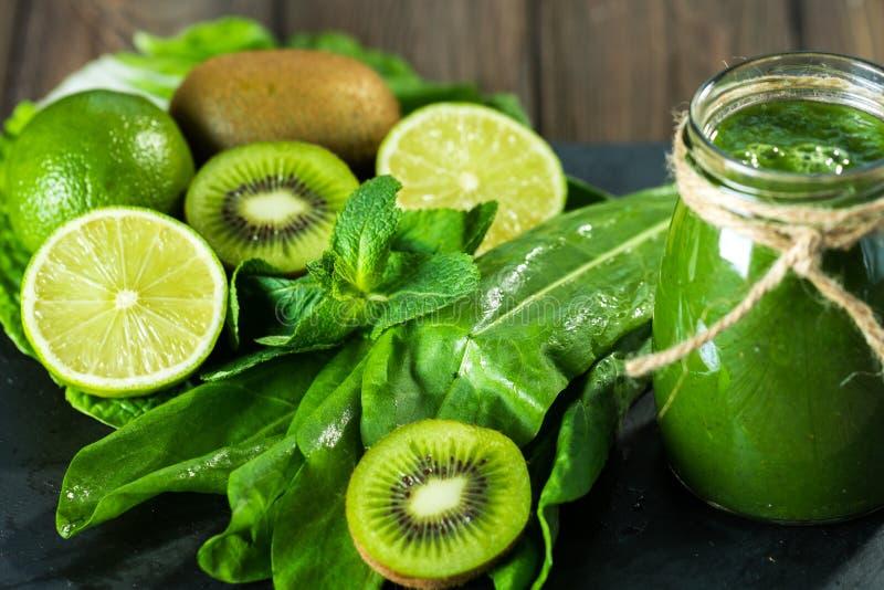 Gemengde groene smoothie met ingrediënten op de steenraad, houten lijst royalty-vrije stock fotografie