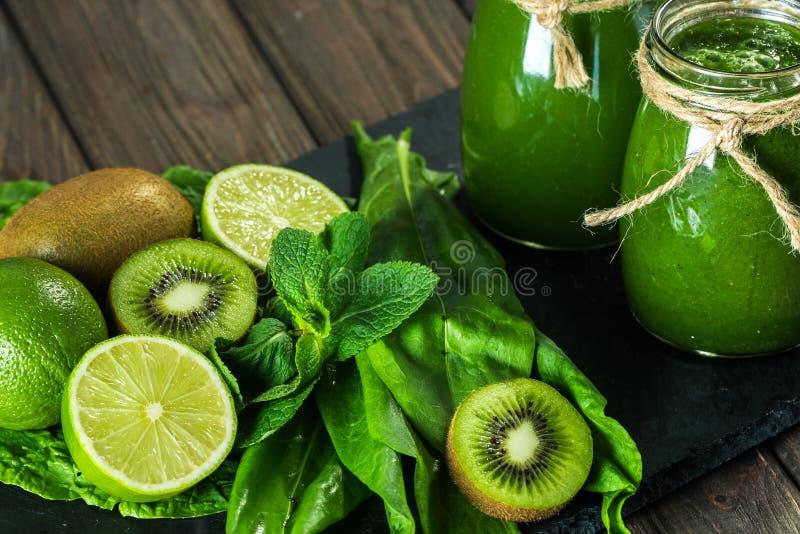 Gemengde groene smoothie met ingrediënten op de steenraad, houten lijst stock fotografie