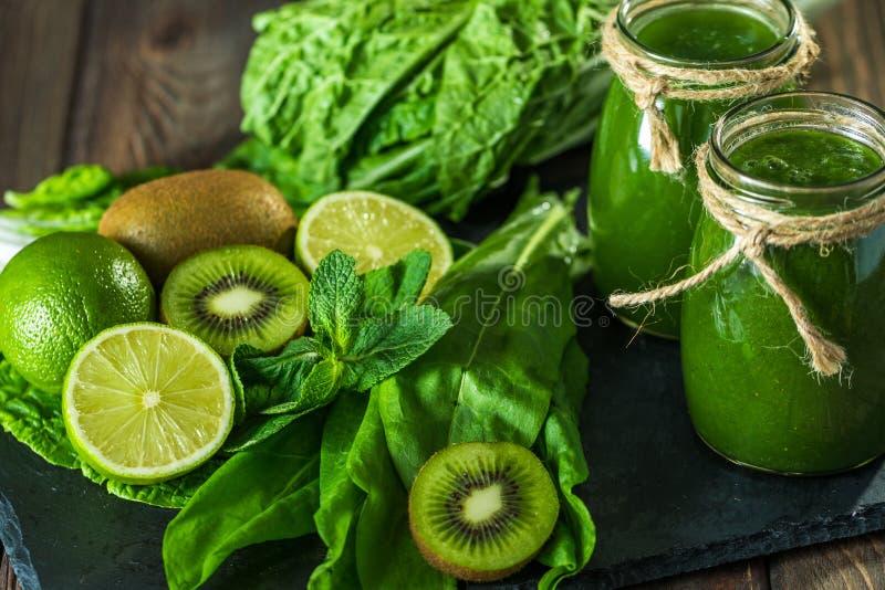 Gemengde groene smoothie met ingrediënten op de steenraad, houten lijst stock afbeelding