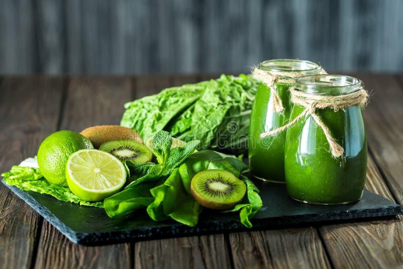Gemengde groene smoothie met ingrediënten op de steenraad, houten lijst royalty-vrije stock afbeelding