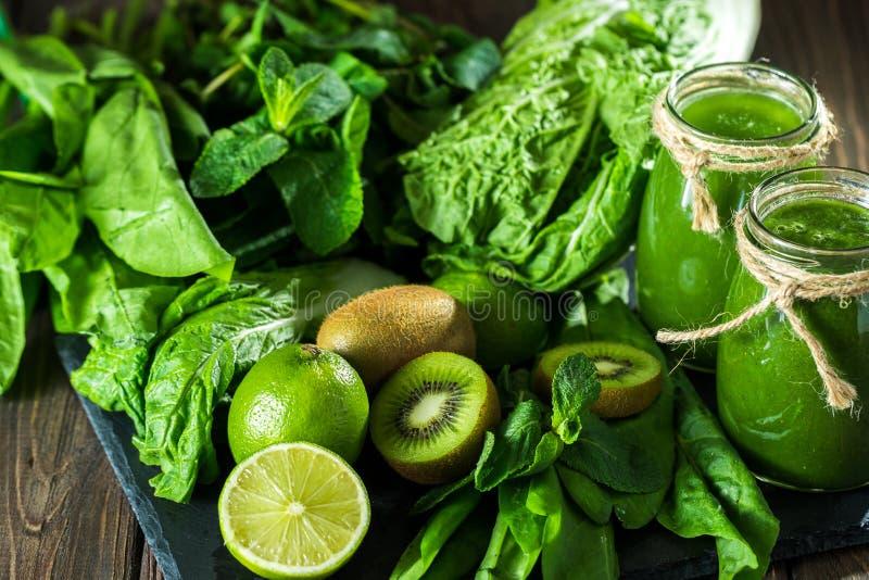 Gemengde groene smoothie met ingrediënten op de steenraad, houten lijst stock foto