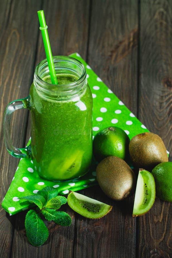 Gemengde groene smoothie met ingrediënten op houten lijst selectiv stock afbeeldingen