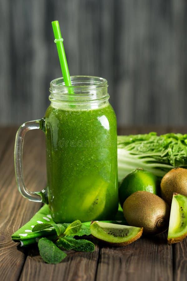 Gemengde groene smoothie met ingrediënten op houten lijst selectiv royalty-vrije stock afbeeldingen