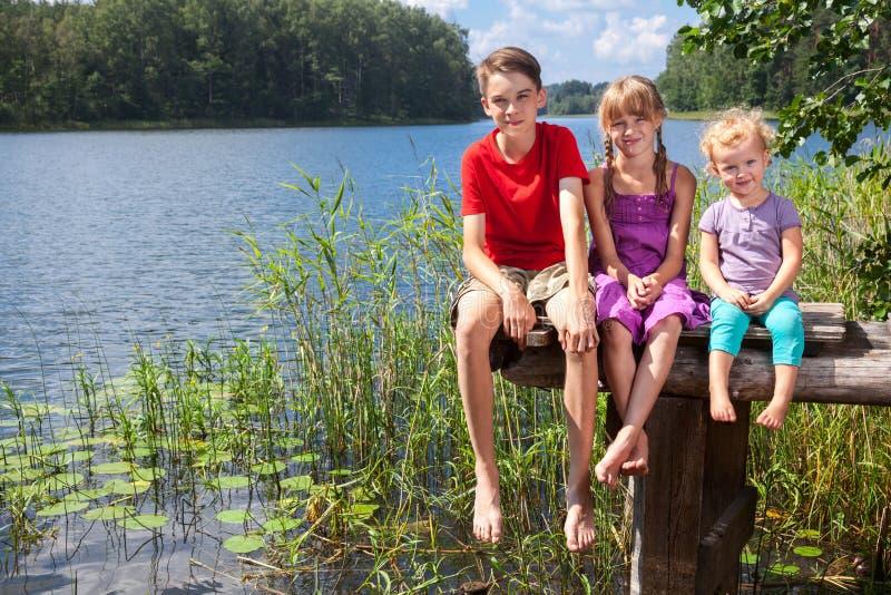 Gemengde leeftijdskinderen die op een pijler door een de zomermeer zitten stock foto's