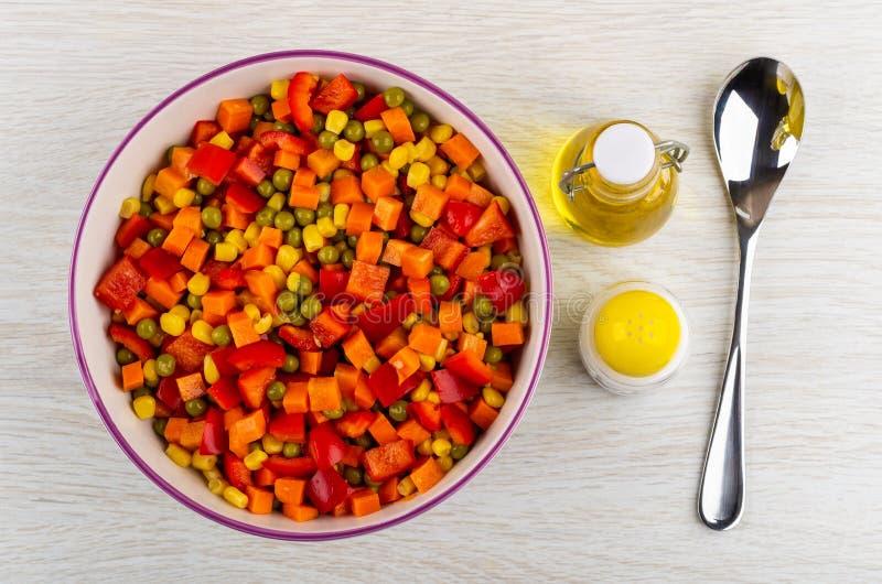 Gemengde paprika, wortel, groene erwten, graan in ceramische kom, fles plantaardige olie, zout, lepel op lijst Hoogste mening stock foto's