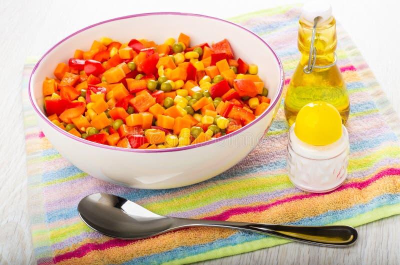 Gemengde peper, wortel, groene erwten, graan in ceramische kom, fles plantaardige olie, zout, lepel op servet op lijst royalty-vrije stock afbeeldingen