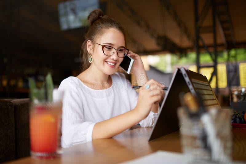 Gemengde race die freelancer met convertibele laptop werken en op cellphone met cliënt in koffie spreken Aziatische Kaukasisch stock foto