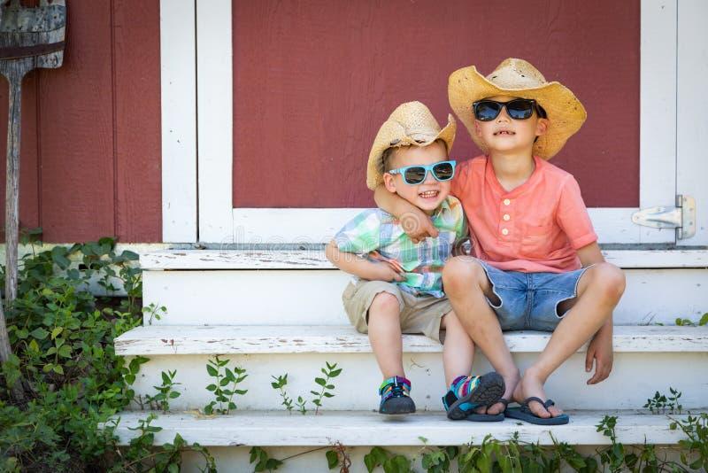 Gemengde Ras Chinese en Kaukasische Jonge Broers die Pret hebben die Zonnebril en Cowboy Hats dragen royalty-vrije stock afbeelding