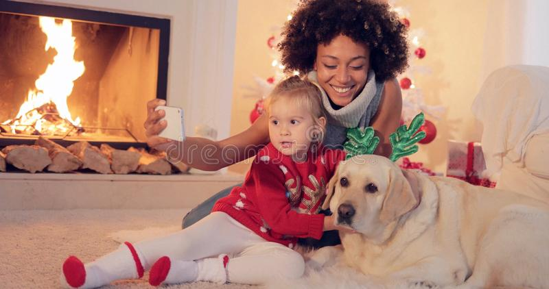 Gemengde rasfamilie die Kerstmis nemen selfie stock fotografie