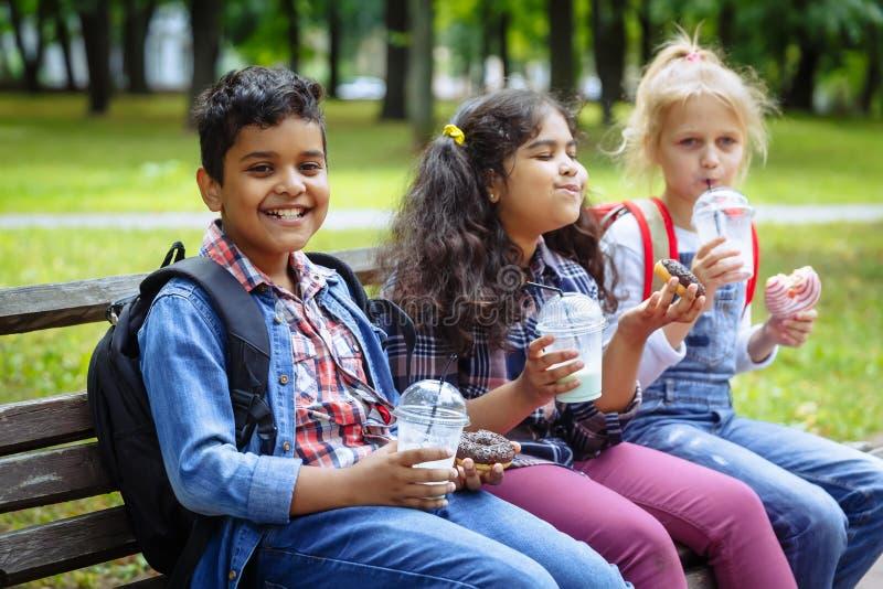 Gemengde Rassengroep schooljonge geitjes die lunch samen op onderbreking eten in openlucht dichtbij school Terug naar het Concept stock foto